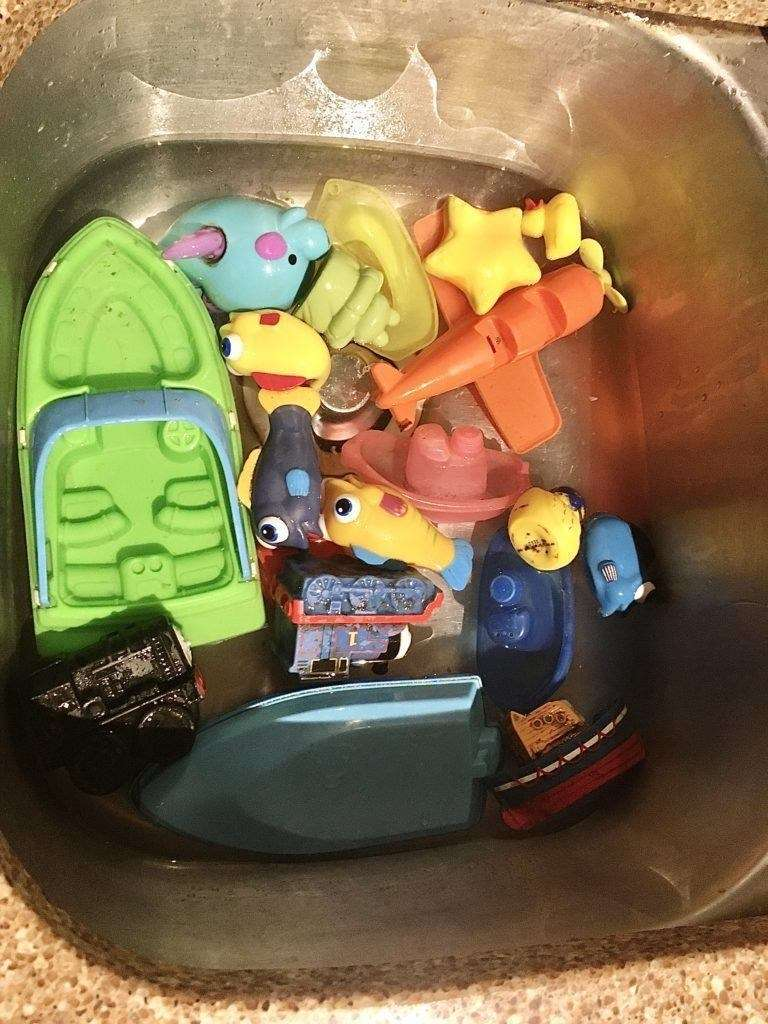 Bath toys in a vinegar solutions in a stainless steel kitchen sink