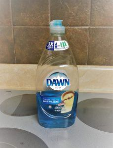 A bottle of blue Dawn detergent sitting on a smooth stovetop