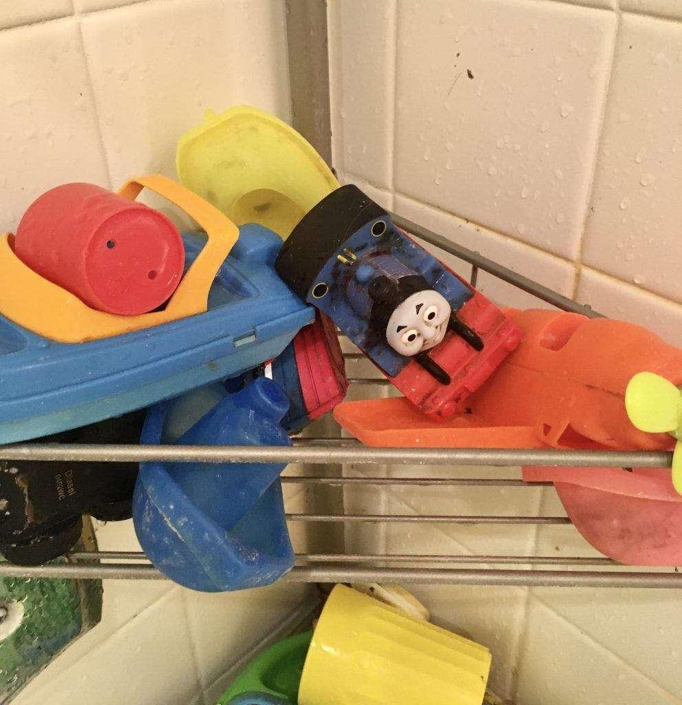 Dirty bath toys on a wire shelf in bathtub