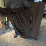 person in gray sweater holding brown fitted bed sheet in front of her. One end of sheet in each hand