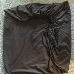 Brown fitted sheet partially folded laying on carpet