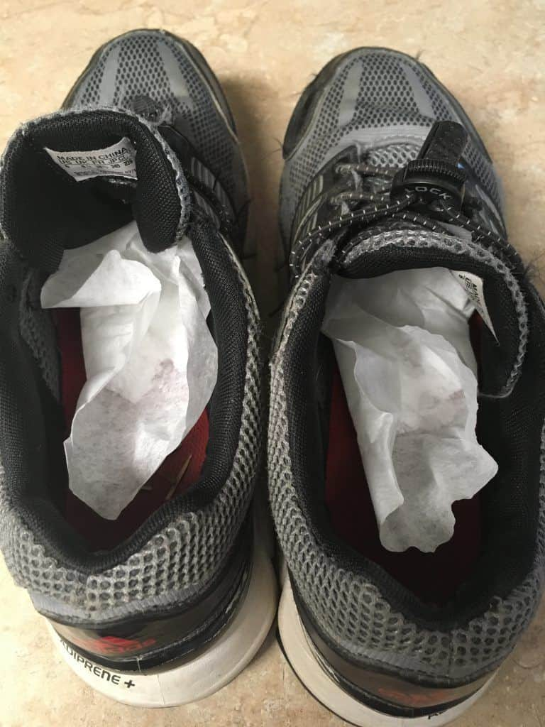 Running shoes with coffee filters inside sitting on a counter