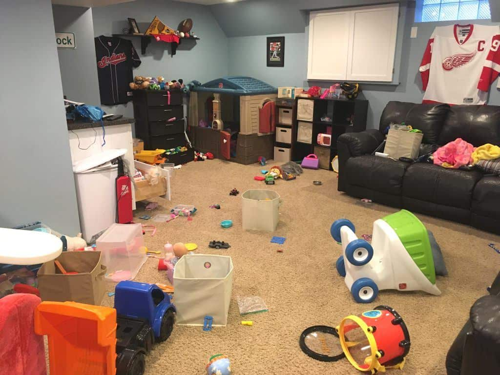 Messy room with toys all over the carpeted floor and black couch. Toys include trucks, drum, blankets, playhouse, play food, stuffed animals