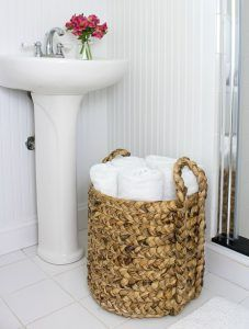 Wicker basket full of rolled white towels on white tile bathroom floor with pedestal sink