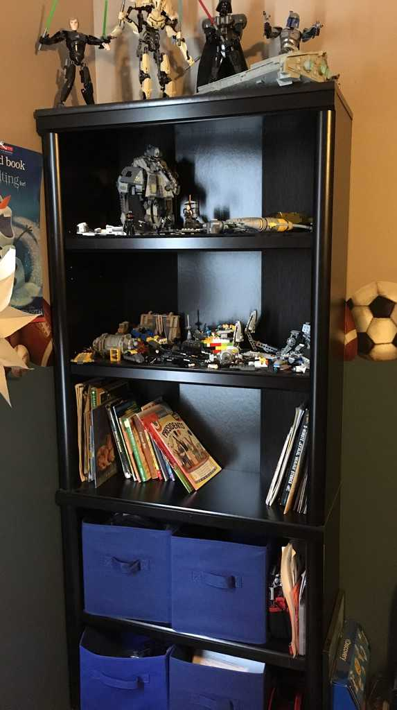 Black bookcase with Star Wars lego figures, books, and blue fabric bins