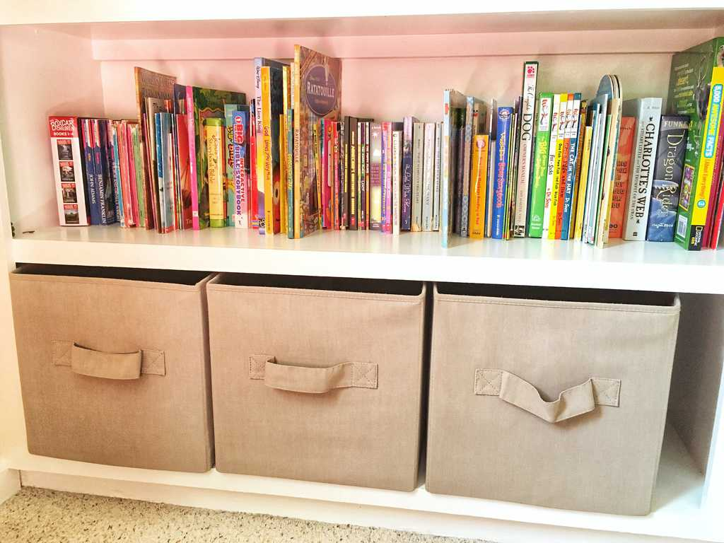 books on a white wooden built in book shelf with fabric storage totes on bottom shelf