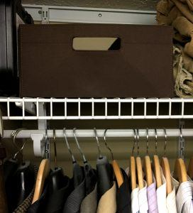 Brown fabric bin on top of white wire shelf with hanger hanging on white rod below
