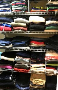 Wire shelving racks in closet with folded clothes on the shelves