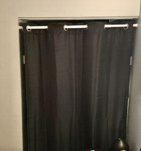 Gray curtain covering small closet