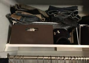 Brown fabric storage bin with white wire shelf on closet shelf