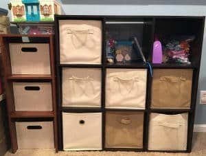 Wood storage cube organizer with cream and brown fabric storage totes and toys on it