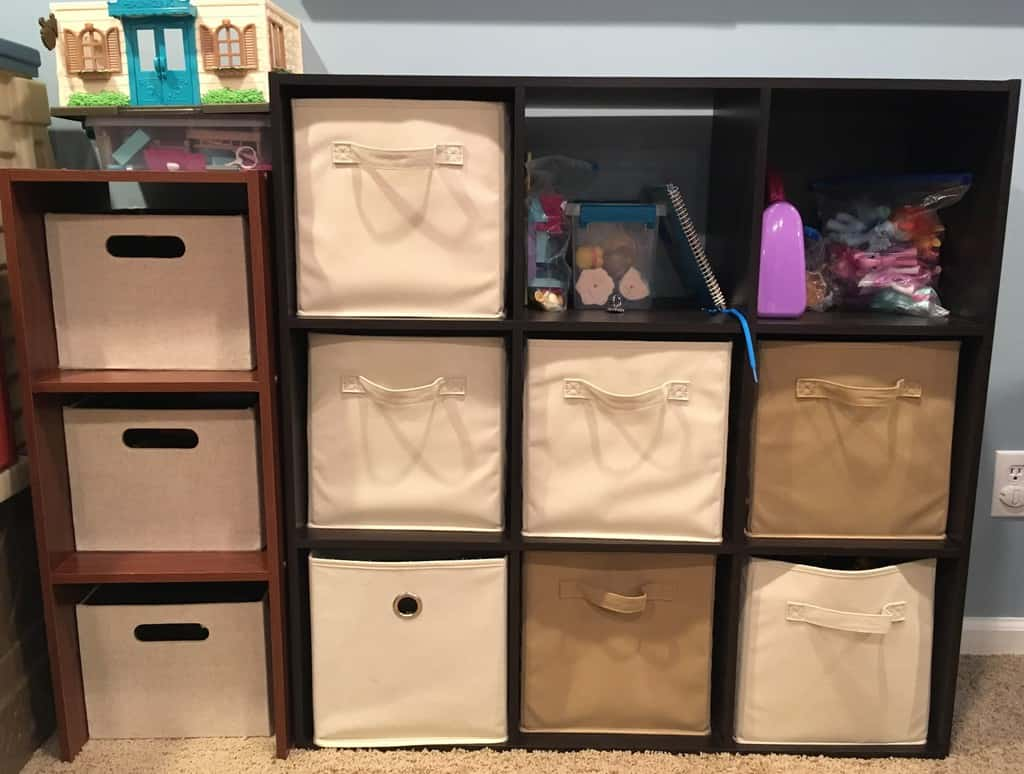 Cube storage with beige fabric cubes filled with toys.
