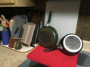 Dishes, utensils, pots drying on red and cream drying mats on a countertop and flat stovetop