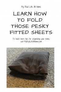 Brown folded fitted bed sheet on tan carpet
