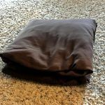 folded brown fitted bed sheet on carpet