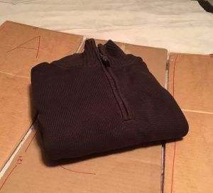 Brown sweater folded neatly on a cardboard clothes folder