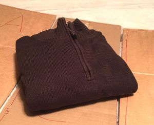 Neatly folded brown sweater on top of a handmade cardboard clothes folder