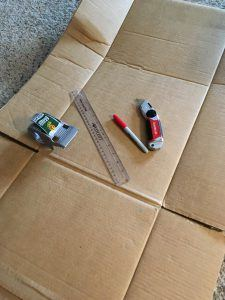 Supplies to make a clothes folder - cardboard, ruler, marker, tape, knife