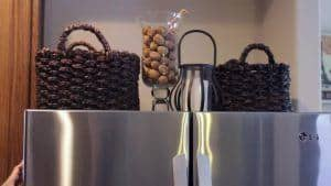 2 wicker baskets on top of stainless steel fridge