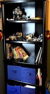 Black bookcase with legos, books, and blue fabric storage bins on the bottom two shelves