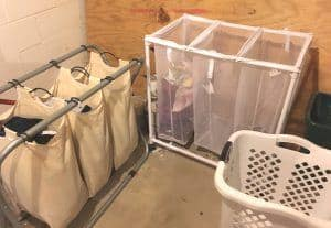 Two Fabric divided laundry hampers and a plastic laundry hamper on a concrete floor