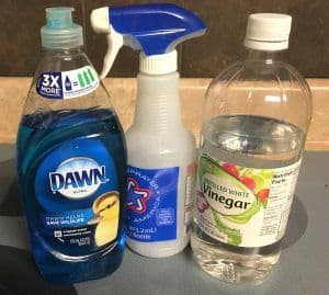 Bottle of Dawn detergent, empty spray bottle and bottle of vinegar on smooth stove top.