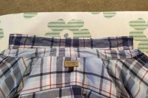 Inside of blue plaid shirt and collar on an ironing board