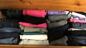 Kids pants folded neatly in a wood drawer