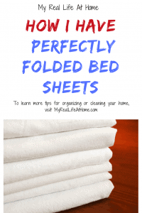 folded white bed sheets on wood table