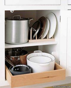 pots and lids in a cover. lids are standing in a rack