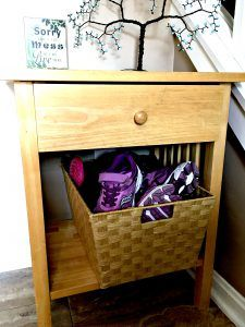 wood side table with wicker basket full of shoes on bottom shelf.