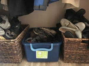 2 wicker baskets and 1 plastic tote full of shoes on tile floor