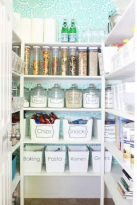 pantry with clear storage containers and white bins, all labeled