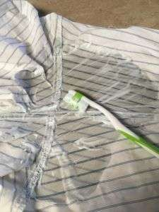 White shirt with blue stripes. Green toothbrush laying on the shirt. Wet spot from cleaning solution on the shirt.