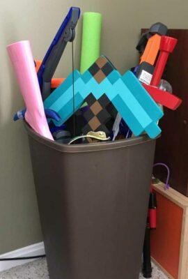 brown plastic garbage pail storing pool noodle, light saber, minecraft pick ax, nerf guns